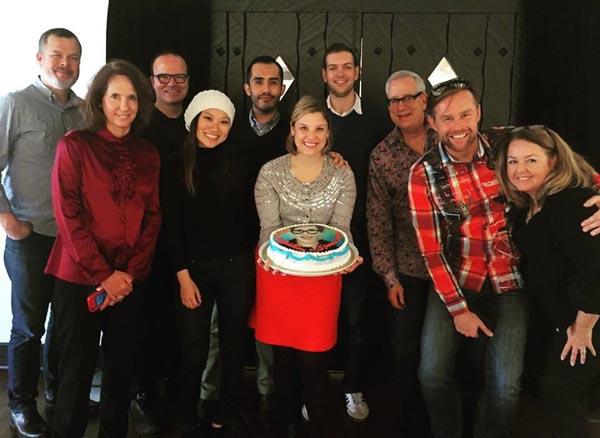 Team member celebrating with a cake