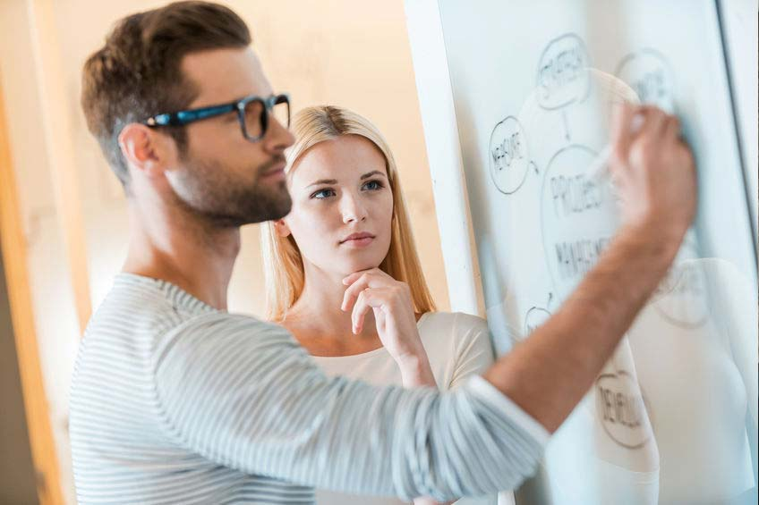 Women watches man write on whiteboard