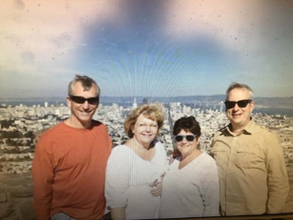 2 men and 2 women pose for photo above city